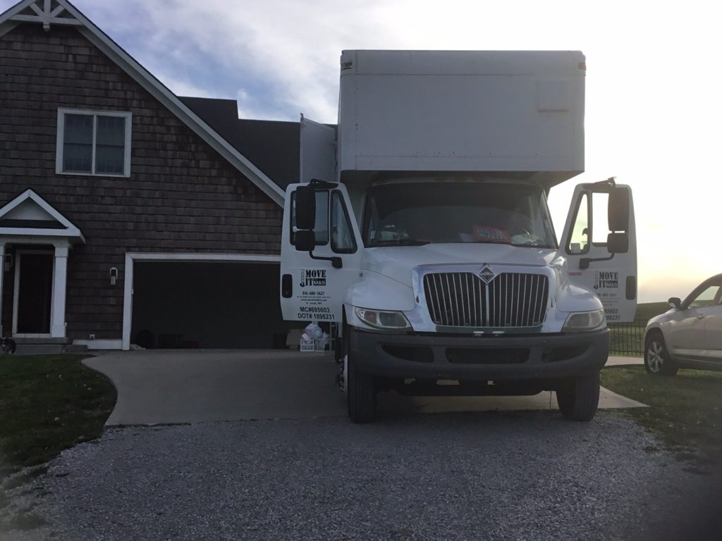 A large moving truck in front of a red brick house