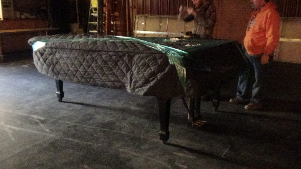 A piano, partially wrapped in preparation for moving