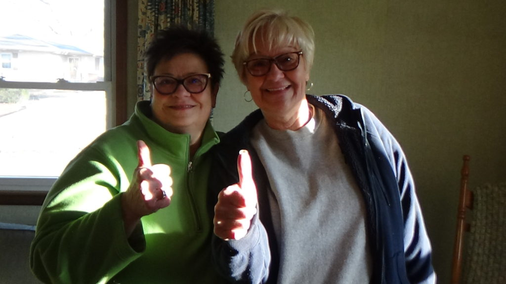 Two women giving the camera a thumbs-up as they smile