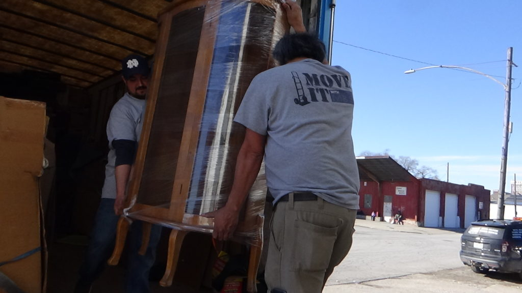 Two of our legitimate mover helpers moving a large china cabinet into the back of a moving truck - checking credentials for insurance is vital!