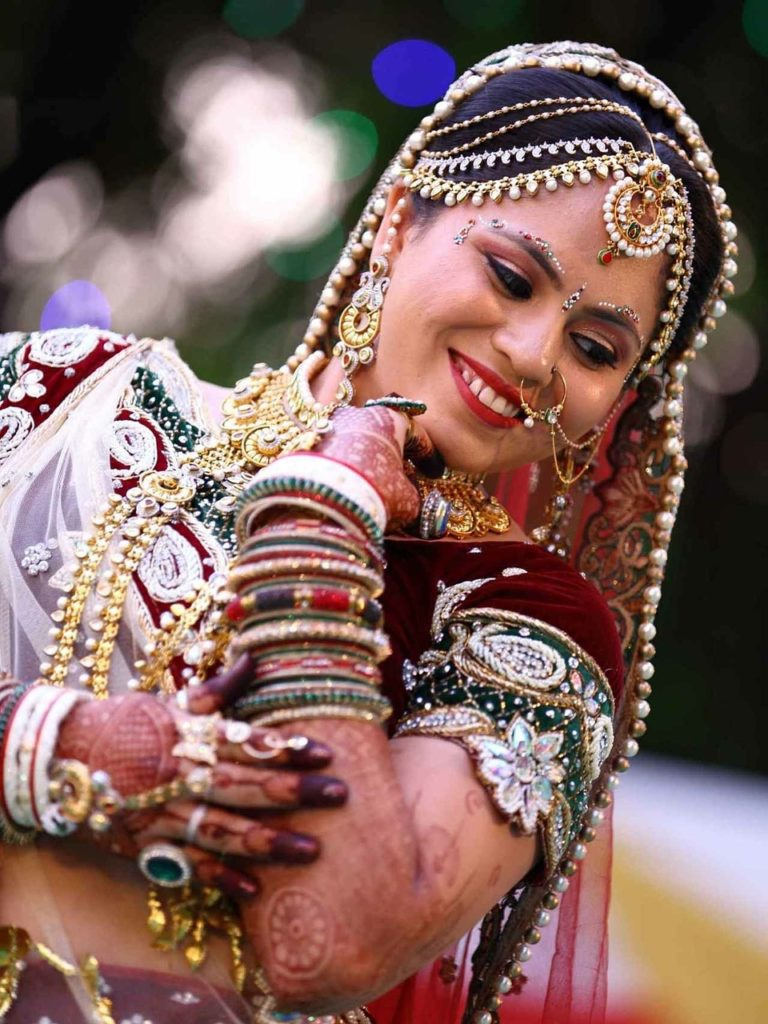Indian woman smiling, dancing while wearing a whole lot of jewelry