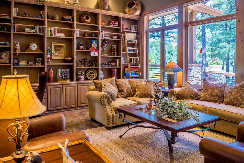 A well-appointed room with built-in bookshelves full of tchotchkes and books, and a lovely sitting area around a glass coffee table atop a gorgeous oriental rug