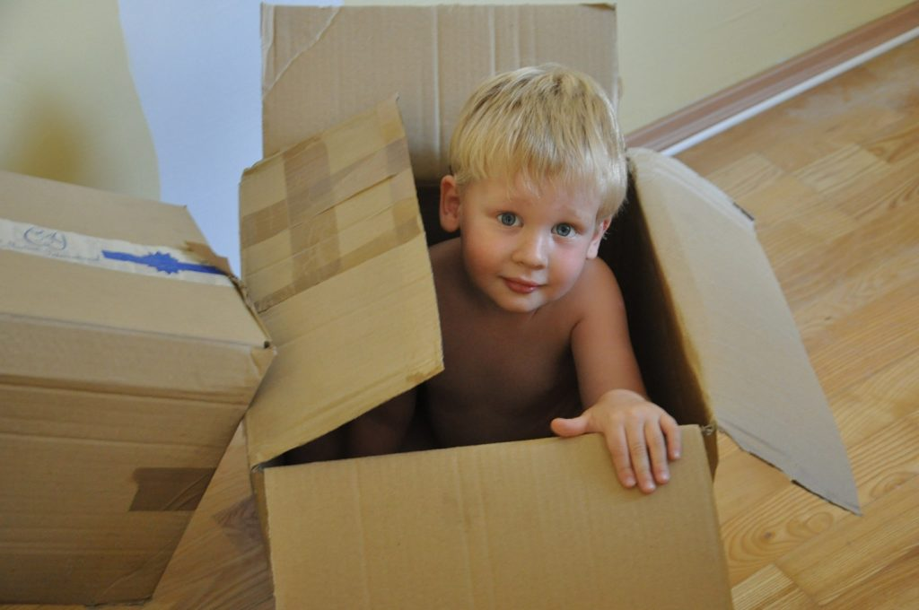 A young boy playing inside a moving box