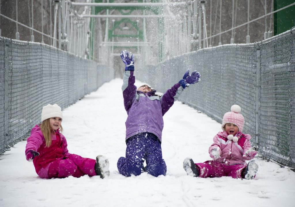 three children playing in the snow