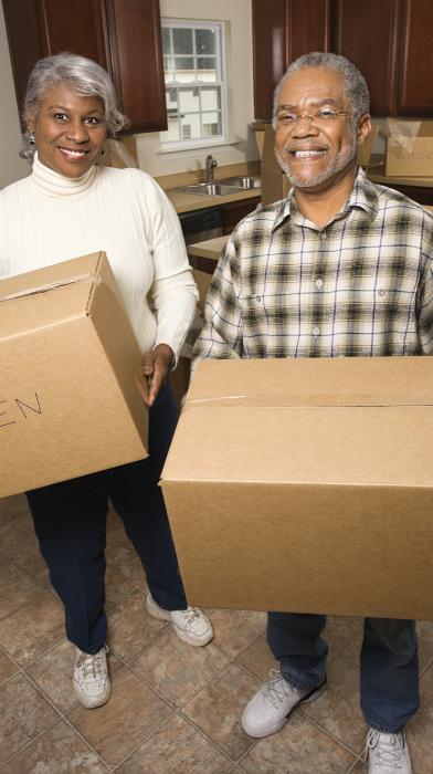 a Black senior citizen couple holding moving boxes