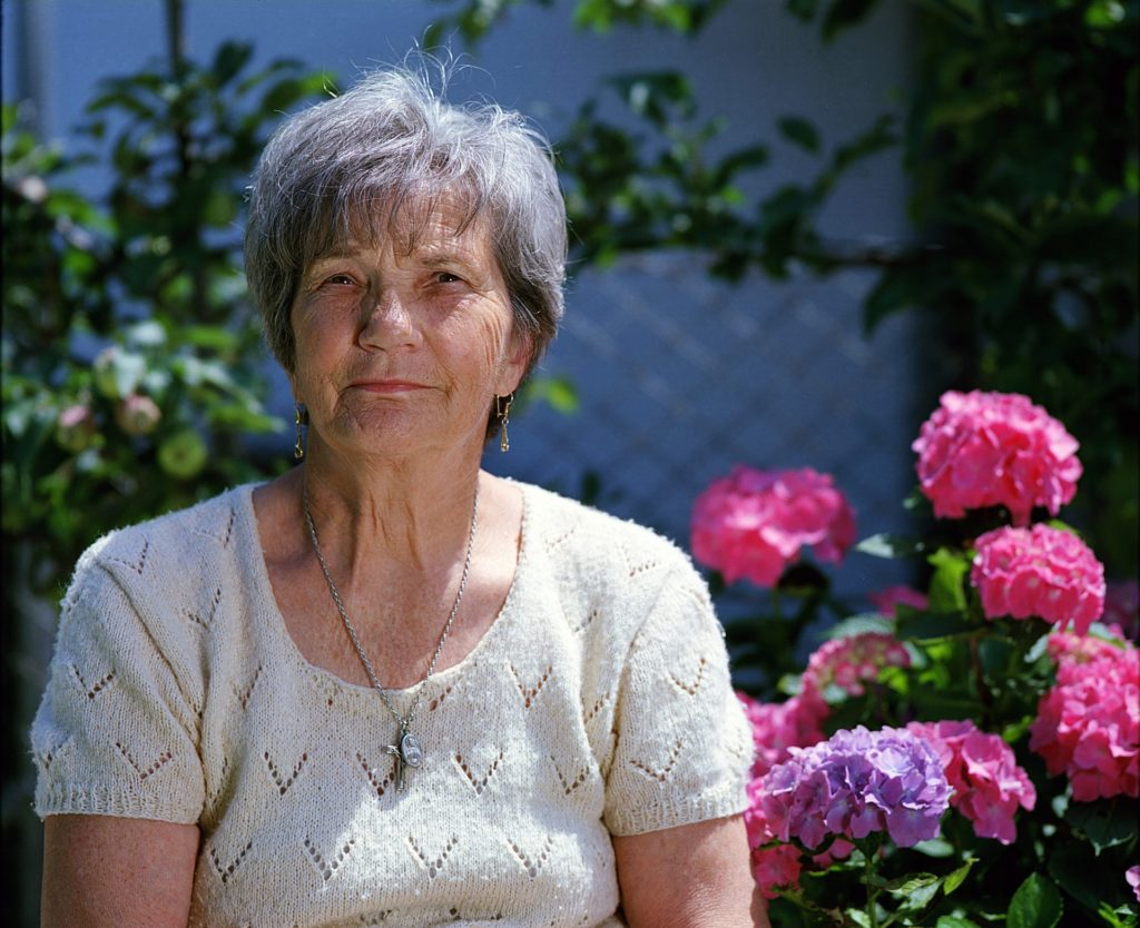Senior woman sitting next to colorful flowers